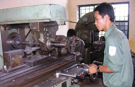 Công nhân đứng điều khiển máy móc